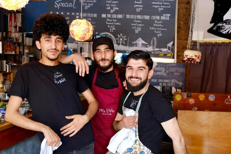 The photo shows three men smiling in a cafe, they are all refugees who have made a success of their new business in the UK