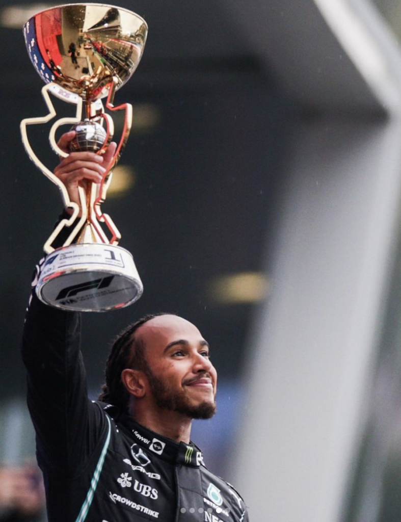 Lewis Hamilton poses with a trophy