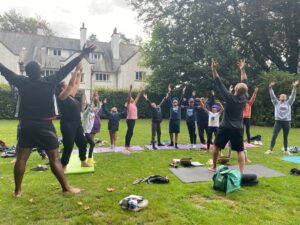 A group of Black and Brown Young People taking part in a yoga class outside on the grass